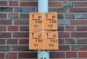 Vier orangefarbene Schilder befestigt an einem Laternenmast