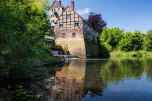 Das Bild zeigt die Havichhorster Mühle, ein Fachwerkhaus an einem See mit einem Wehr.