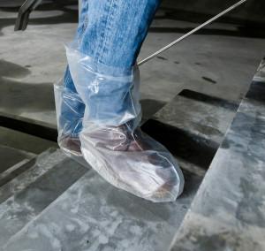 Kleine Plastiktüten über den Schuhen sorgen dafür, dass der Schmutz unter den Sohlen draußen bleibt.