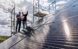Das Bild zeigt eine Photovoltaik-Anlage auf einem Dach und zwei Stadtwerke-Mitarbeiter auf einem Baugerüst.