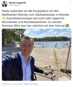Screenshot einer Twitternachricht mit einem Foto: Heute verkündigen wir die Kooperation mit den Stadtwerke Münster zum Glasfaserausbau in Münster (Daumen hoch-Emoji). Zukunftstechnologie und noch mehr Speed Münsteraner und MÜnsteranerinnen. Zu solchen terminen fährt man hier natürlich mit dem Fahrrad. Das Foto zeigt ein Selfie von Herrn Hagsihl mit Fahrrad am Aasee.